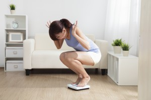 Upset woman on weigh scale